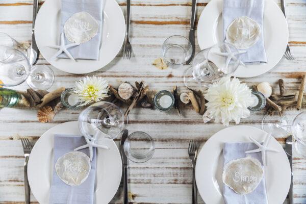 Tisch-Deko mit Schwemmholz: Draufsicht auf vier Gedecke, in der Mitte Juteband geschmückt mit Elementen aus dem Meer